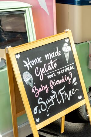 Gluten free, lactose free, gluten free ice cream sign. Advertisement on chalk board during food festival. Vintage retro italian car behind the sign. intolerance free dessert shop directional ad text