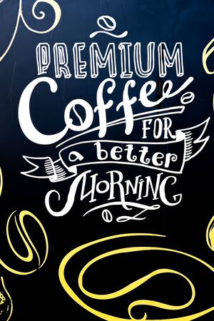 Premium coffee for a better morning chalk board message with white and yellow, on the back of a coffee van truck. Handwritten artistic copy text, motivational and inspirational message