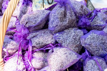 Pouch with lavender in a wooden basket. Fragrant bag of lavender flowers. Sprigs of lavender near the bag with Lavender. Selective focus. Street market.