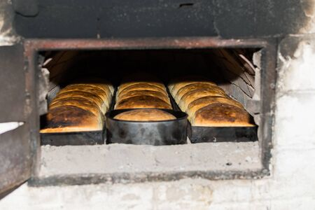 Fresh and crunchy home made bread, baked in traditional stone wood oven. Homemade fresh and crusty wheat dough bread, prepared in firewood, natural and rustic stove, in rural or countryside area Imagens