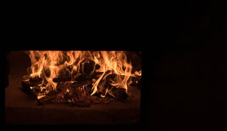 Fire and burn coals in stone oven. Oven made of brick and clay on the wood. Oven for pizza. Brick oven. big burning flames isolated on black, copy space