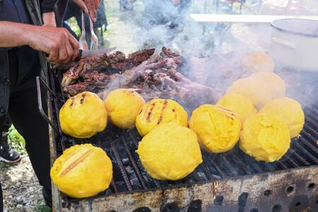 Balls of polenta and cheese in the middle of it, named bulz, a traditional romanian dish. Roasting polenta and cheese on a grill outside, with sheep sheep herding