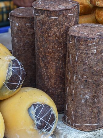 Branza de burduf, traditional sheep's milk cheese from south of Transilvania, Romanian specialty cheese, yellow round shape goat cheese balls homemade, tree bark covering, colored napkin Banco de Imagens
