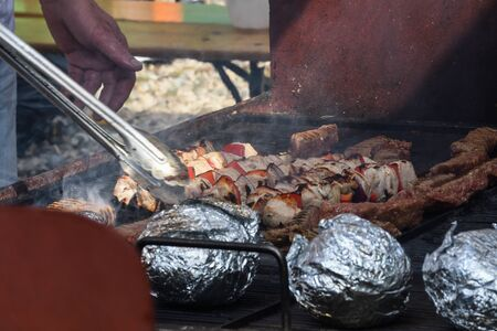 Chef grilling meat during cookout picnic or food event. Meat mix variety:sausages, pork, chicken, lamb, sheep, sardines, fried or grilled, unhealthy protein concept. oily food, cancerigen food