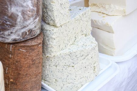A sliced piece of cheese with dill and spices, for sale on counter top, during food festival. Traditional dairy produce made from fresh cow or goat milk, served as an appetizer, cheese cuts in square