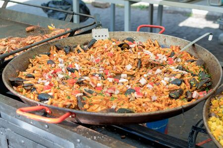 Fresh seafood penne tomato pasta cooking in large wok pan during hotel brunch buffet outside outdoor in the garden by the pool. Fresh Food Buffet Brunch Catering Dining Eating Party Sharing Concept