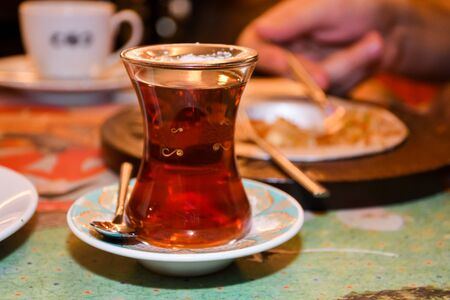 Turkish tea in traditional glass on tray closeup. Black tea specialty served in a restaurant background setting