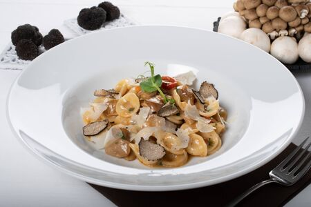 Orecchiette pasta with ceps, cherry tomatoes, ricotta gratin, fresh truffles and wild mushrooms. Orecchiette are a pasta typical of Apulia, a region of Southern Italy.