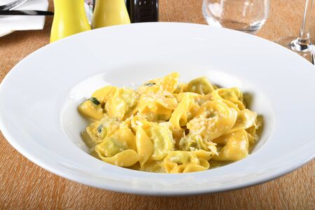 Tortellini with ricotta cheese and spinach, butter, sage sauce, grated parmesan. Parmigiano-Reggiano flakes over traditional italian pasta cooked, served in white plate, over brown table in restaurant Zdjęcie Seryjne