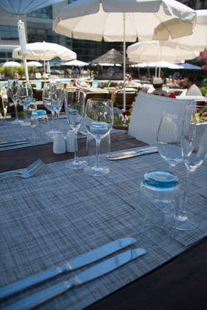 Table setting outdoor terrace. Nobody in the picture just table setup with cutlery and glasses. Pool with sun beds in the background. Blue and wood table, white chairs, summer time and sunshine Standard-Bild