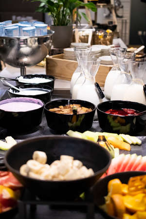 Selection of self service catering continental breakfast buffet display, catering or brunch table food buffet filled with fresh fruits, cereals and milk in a hotel or restaurant setting Standard-Bild