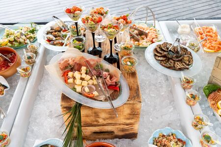 Luxury catering by the pool, food bloggers event, banquet, wedding, festive, hotel brunch buffet arrangement with clean simple design, decorations, boat filled with ice. Modern design and decorations