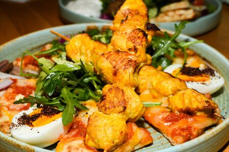 Chicken tandoori with rucola salad, egg with sumac spice, pitta bread. Asian dish served in a restaurant setting Stock Photo