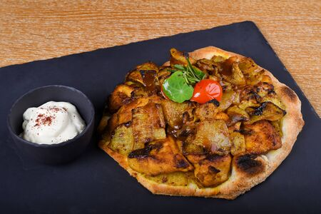 Baked chicken tights and served on a pita bread or focaccia pizza dough, restaurant setting. Condiments like sumac, tandoori spices, fried onion. East Mediterranean food, Lebanese or Levantine
