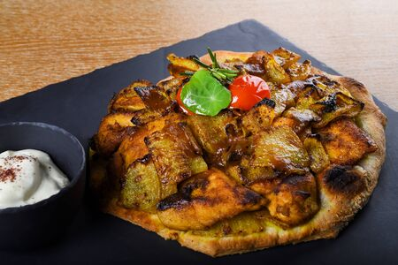Baked chicken tights and breast served on a pita bread or focaccia pizza dough, restaurant setting. Condiments like sumac, tandoori spices, fried onion. East Mediterranean food, Lebanese or Levantine