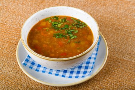 Fresh lentil soup in a white bowl, served in a restaurant setting, selective focus. Fresh Food Catering Dining Eating Party Sharing Concept, food delivery menu
