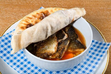 Fish stew in a white bowl, served with a pita bread cover on top. Levantine East Mediterranean food