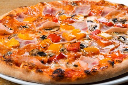 Pizza capricciosa is a style of pizza in Italian cuisine prepared with mozzarella cheese, Italian baked ham, mushroom, artichoke and tomato, edible mushrooms, cremini, prosciutto, marinated artichoke.