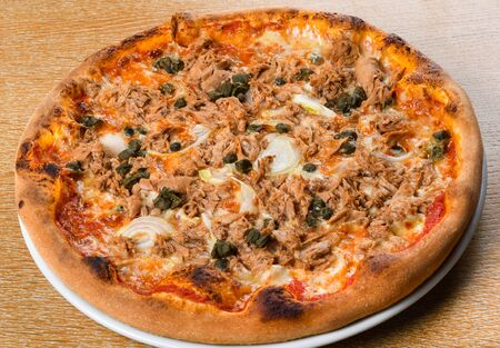 pizza tonno e cipolla: this traditional pizza variety is topped with tomato sauce, mozzarella, tuna, and sliced onions. It is often sprinkled with oregano. Fresh Food Catering Dining Eating concept