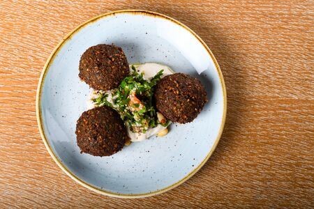 Falafel is a deep-fried ball, or a flat or doughnut-shaped patty, made from ground chickpeas, fava beans, or both. Herbs, spices, onion. Middle Eastern dish that most likely originated in Egypt.