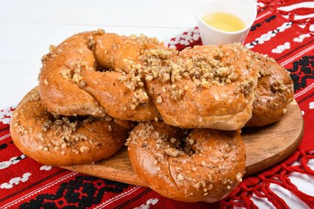 Concept of romanian cuisine. Homemade Mucenici, traditional desserts made in the figure 8 to look like garlands, smeared with honey and chopped nuts.