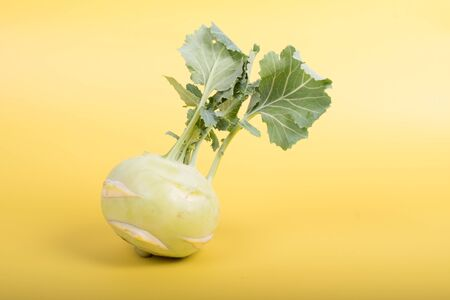 Three pieces of kohlrabi vegetable isolated on yellow simple background with copy space. Green leafy vegetable from cabbage and radish family, bio and organic grown from the garden