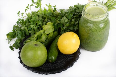 Jar of raw green vegetable smoothie juice with lemon, cucumbers, apple, apio and parsley, on white background Reklamní fotografie