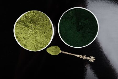 An isolated tablespoon of dried organic wheat grass and spirulina powder, on white or rustic background. Healthy living, detox recipes, raw vegan smoothie or juice ingredients