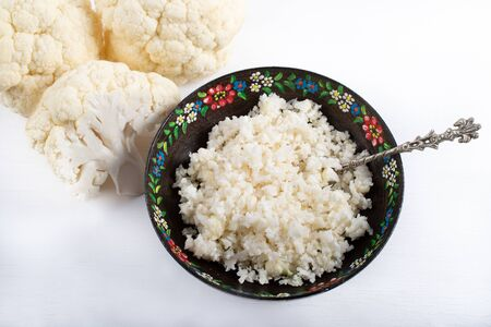 Paleo organic vegetarian food cauliflower rice in a floral rustic bowl, on white background
