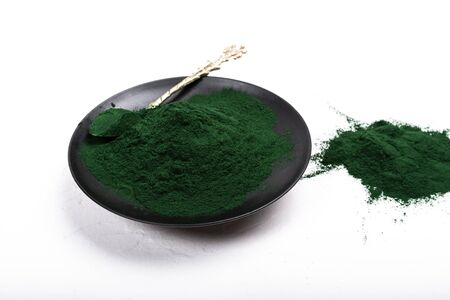 An isolated tablespoon of dried organic spirulina algae powder, on white or rustic background. Healthy living, detox recipes, raw vegan smoothie or juice ingredients