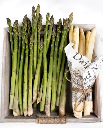 Green and white asparagus. Local produce for sale displayed at the market. Borough farmer's market in London. Organic and bio fresh healthy eating concept. Veggies, vegetables, herbs and spices, price