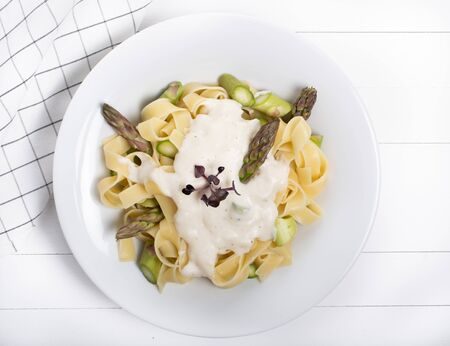 Fresh homemade pasta dish of fettuccine or tagliatelle, green asparagus, white sauce, in a white plate on wooden white background table