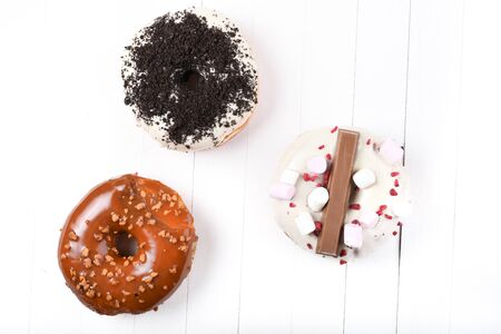 Three melted glazed with dark and white chocolate, marshmallows, biscuit crumbles, caramel sugar coated donuts on white wood board Фото со стока