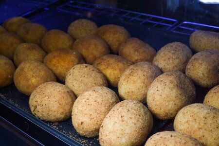 Arancini (deep fried rice balls with meat) Typical Sicilian street food at market in Italy. Lots of fried rice balls for sale in street food stall