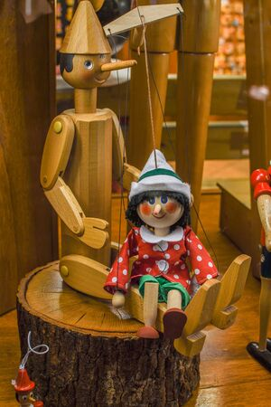 Wood toy Pinocchio. Workshop where the master scrutinizes the handmade traditional wooden toys of Pinocchio