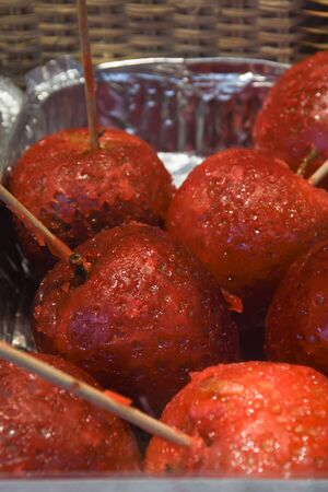 Sweet glazed red toffee candy apples on sticks for sale on farmer market or country fair. Thanksgiving and Halloween homemade red caramel glazed toffee apples with sticks Standard-Bild