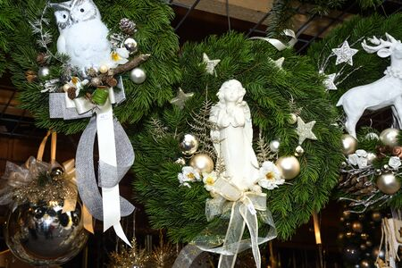 Christmas figurines snowman, angels, biblical religious Christmas scenes in fir branch crowns garland natural festive decoration used to be hanged at the door entrance of the house. 免版税图像