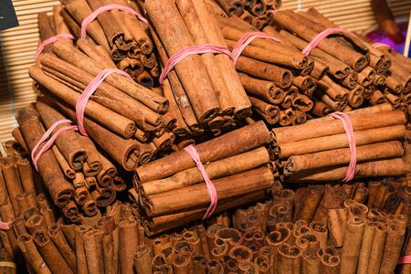 Bunch of cinnamon sticks for sale on counter top at the Christmas market. Healthy aromatic spice used in cooking and medicine, aromatherapy