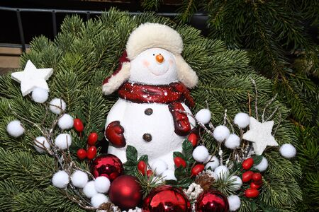 Christmas figurines snowman, angels, biblical religious Christmas scenes in fir branch crowns garland natural festive decoration used to be hanged at the door entrance of the house. 写真素材