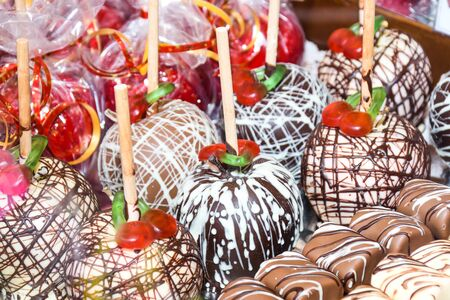 Sweet glazed red toffee candy apples on sticks for sale on farmer market or country fair. Thanksgiving and Halloween homemade red caramel glazed toffee apples with sticks