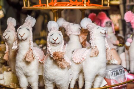 Cute alpaca stuffed toy with small hats smiling for sale in a Christmas market shop