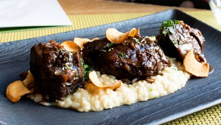 Ossobuco or osso buco is a specialty of Lombard cuisine of cross-cut veal shanks braised with vegetables, white wine and broth. Served with either risotto alla milanese or polenta