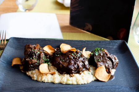 Ossobuco or osso buco is a specialty of Lombard cuisine of cross-cut veal shanks braised with vegetables, white wine and broth. Served with either risotto alla milanese or polenta 스톡 콘텐츠