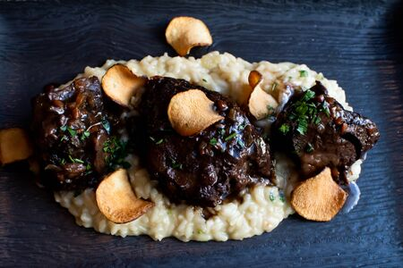 Ossobuco or osso buco is a specialty of Lombard cuisine of cross-cut veal shanks braised with vegetables, white wine and broth. Served with either risotto alla milanese or polenta Zdjęcie Seryjne