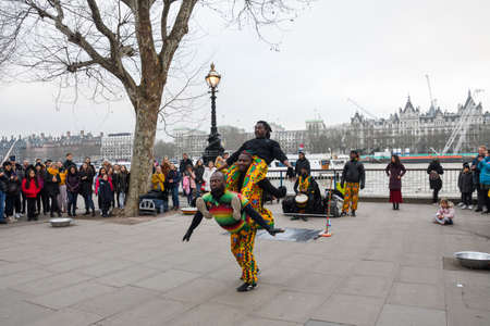 London, United Kingdom, 24th of January 2020: Brazilian acrobatic dancers performing on the street, near London Eye, riverside Thames, with crowd applauding