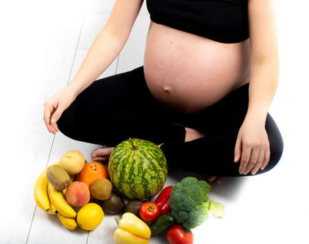Pregnant woman with fruit and vegetables around her. Healthy eating concept. Pregnancy, slim skinny girl in black top and leggings isolated on white background. Diet and freshness