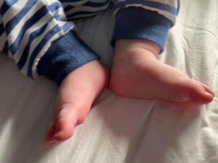 Small baby boy feet, no socks, little foot toes. Cute candid details closeup Standard-Bild