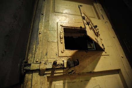 Old, metal, locked door in prison photo