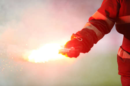 torches: Fireman picks up torches thrown by supporters in a football game