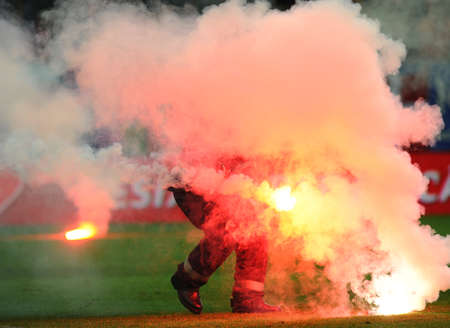 arsonist: Fireman picks up torches thrown by supporters in a football game